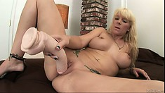 Tattooed blonde with nice tits uses a huge dildo in her dark hole