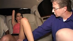 Naughty brunette lets two guys tease her cunt during a limo ride