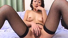 Mature Japanese babe in fishnet stockings plays with her muff