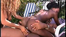 Two sexy black babes gobble up his chocolate bar and get fucked outdoors