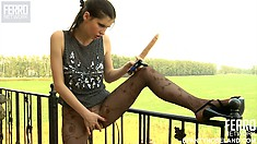 Beatrice enjoys the view from the balcony as she shoves a dildo in her twat