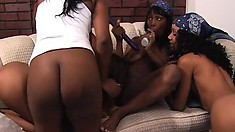 Horny dark skinned babes get together on the couch and enjoy a wild lesbian orgy