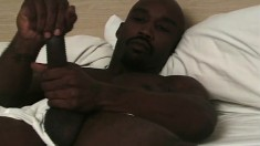 Attractive black stud Bam lies on the bed and pleases his massive dick