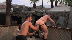 Army gays are outside on the balcony fisting ass up to his arm
