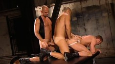 Two kinky studs get their asses fucked by a leather-clad hunk's fists and cock